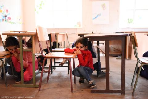 A girl hiding under the table and covering her mouth during the preparedness drills in the school in border village of Nerqin Tsakhkavan.