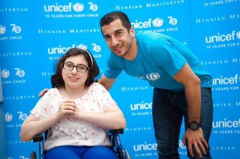 Henrikh Mkhitaryan with a girl who has a disability smiling to the camera.