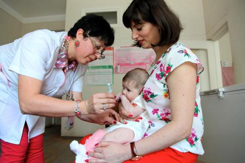 Woman holding her baby while nurse vaccinates