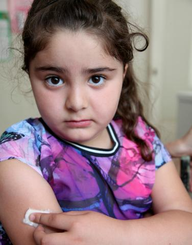 A 6 year old girl looking sadly after she received a routine vaccination at a clinic in Armenia.