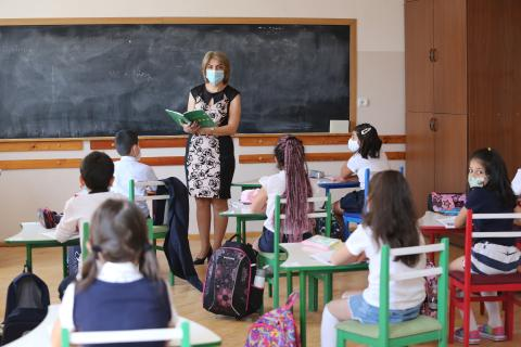 A Teacher wearing a mask explaining the lesson to the class