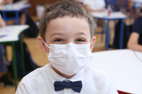 A 2-nd grader, wearing a mask smiling for the camera