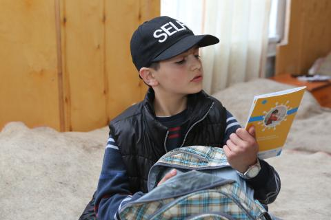 11-year old boy reading the cover of COVID-19 brochure