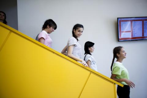 Girls on the stairs and one girl with braided hair looking to the camera.