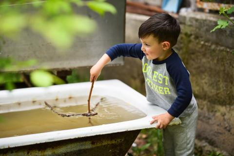 A five-year old boy with a stick in a hand playing with collected rain water