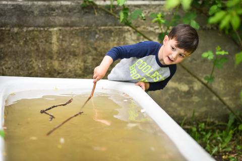 A boy with a stick is playing with collected water in a tab outside