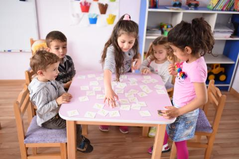 Children are playing with cards around the table in alternative preschool in Shamut village established by UNICEF.