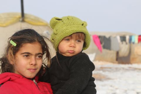 Young girl in a refugee camp holding a toddler