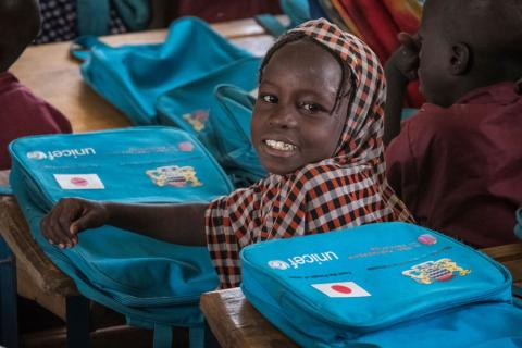 Young girl sitting at a school desk with UNICEF backpack