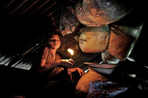 A young girl crouching in attic holding a light