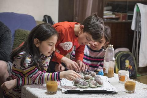 A refugee family from Aleppo, Syria, who found refuge in Yerevan, Armenia. Movses 8, and her brother Meghedi 11, together with their friend Anush are picking cookies from the table.