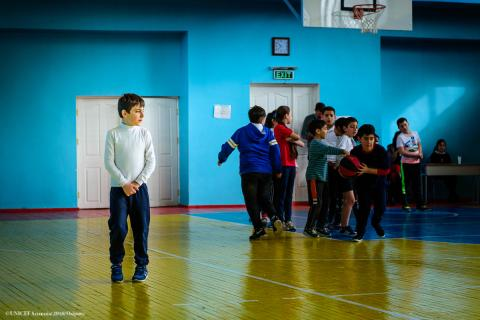 A photo shows a child isolated from his classmates during physical education class.