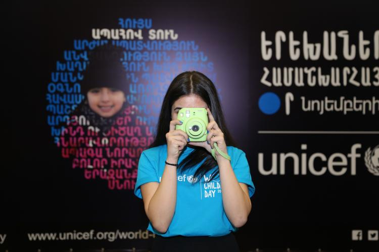 An adolescent is shooting photo during World Childnren's Day event.