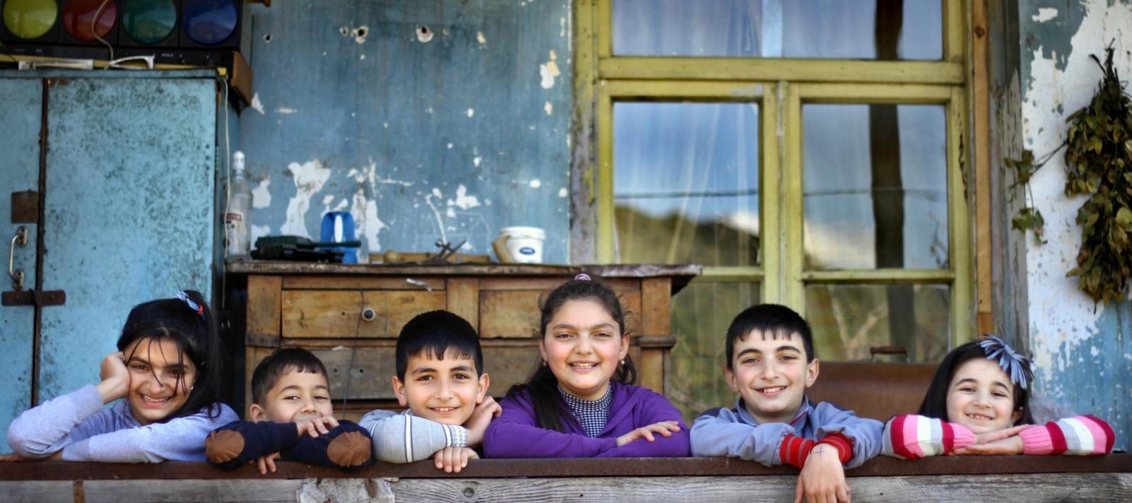Six children standing behind the fences in front of the old building in the village and putting their arms on the fence and smiling.