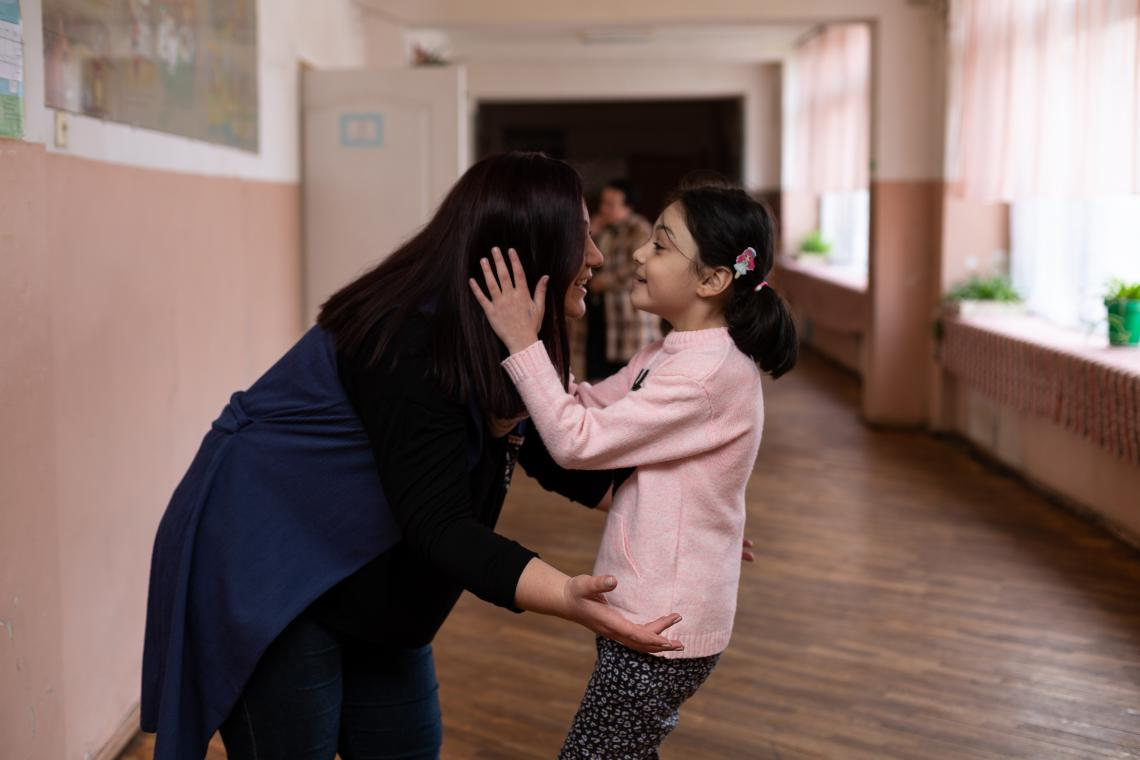 Elena and her mom hugging in the school.