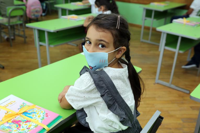 preschool girl wearing a mask during the class