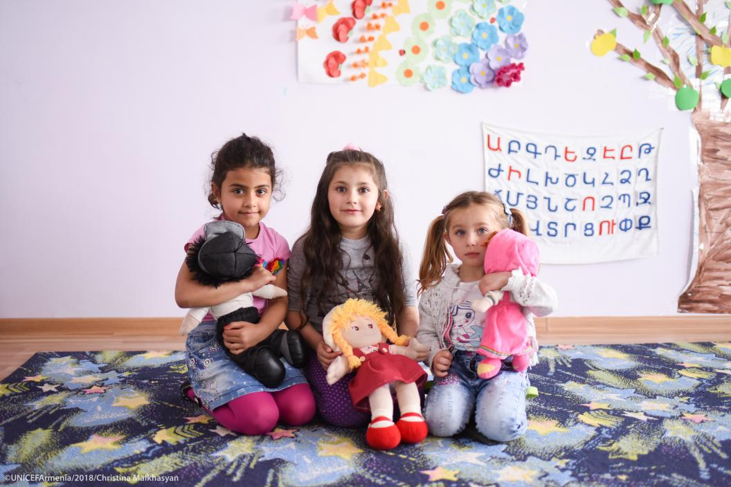 May 2018  Village of Shamut, Lori region, Armenia. Three girls sitting on the floor with their favorite toys in their hands in the preschool. This alternative preschool is developed and established by UNICEF Armenia, ensuring early learning for children in small communities.