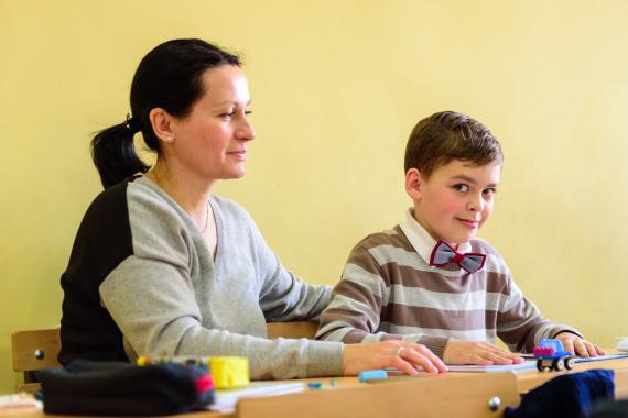 The mother helps her child with autism during the class in inclusive school in Yerevan.