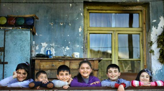 Children stand in a line in front of a house in one of the villages of Armenia.