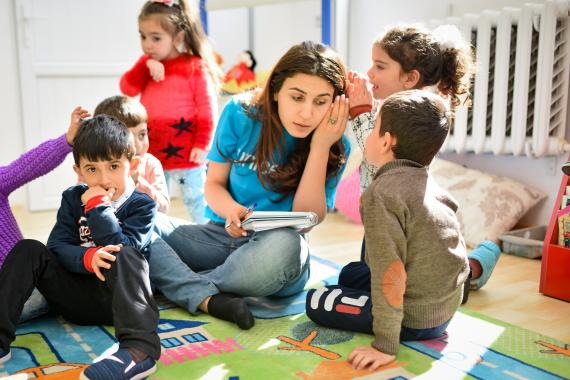 In new alternative kindergarten established by UNICEF Armenia, children sharing their secrets with UNICEF staff member, while sitting on the floor.