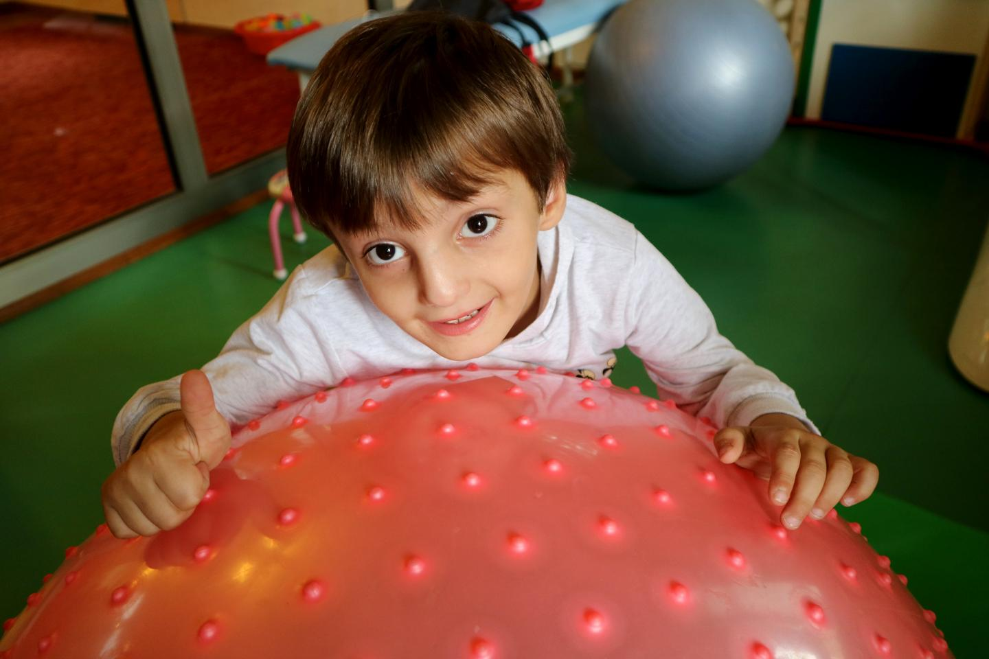 A boy smiling at the centre for children with developmental delays.