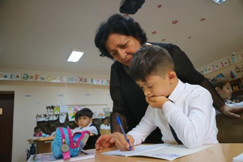 Teacher in her classroom with a child writing.