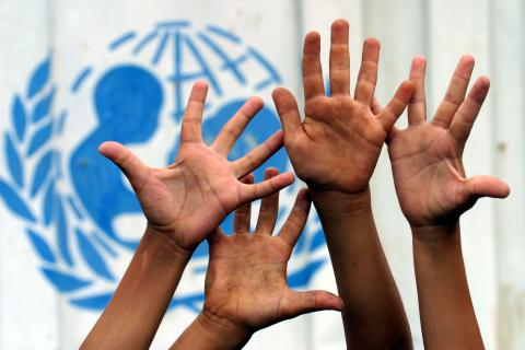 Children`s hands raised in front of a UNICEF emblem.