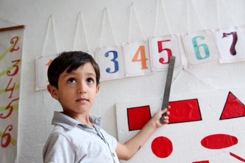 A boy learns how to read numbers.