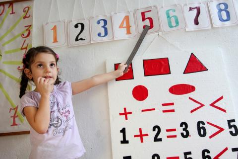 A girl learns to identify numbers on her first day of school after the summer holidays, at UNICEF-supported Preschool.