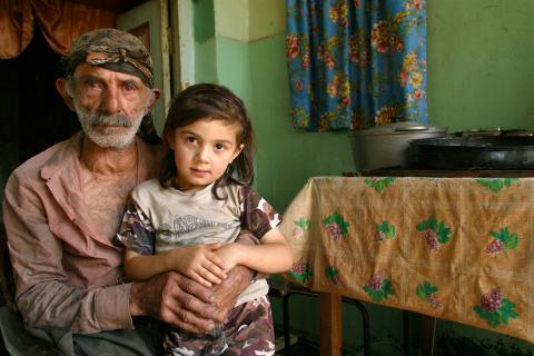 A girl stands by her father at their home.