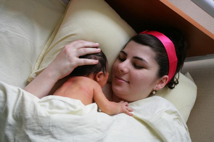 A mother holds her new born baby close at the hospital in Baku