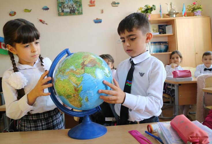 Children are looking at the globe during a class session.