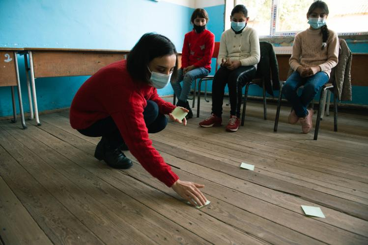 A psychologist places post-it cards on the floor of a classroom as part of the psychosocial support activities.