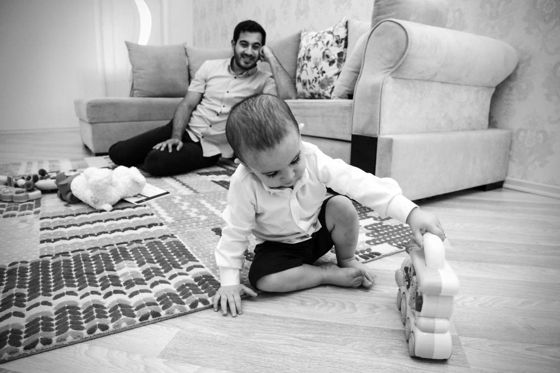 A father watching his baby play with a toy happily.