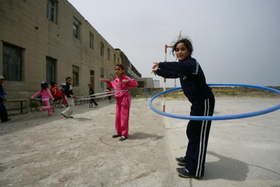 Two girls playing at the school yard of their school.