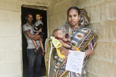 Mussammat Rahmatunessa,28, stands in front of her house with the birth certificate of Mohammad Sinhad Hossain, her newborn baby who is just a few months old in Raipur village, East Birgao Union in Sunamganj on 5 March 2014.