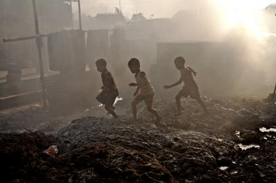 Children play outside their home that has been turned into a large dumpsite by waste from leather industries in Hazaribagh area near Buriganga river in Dhaka.