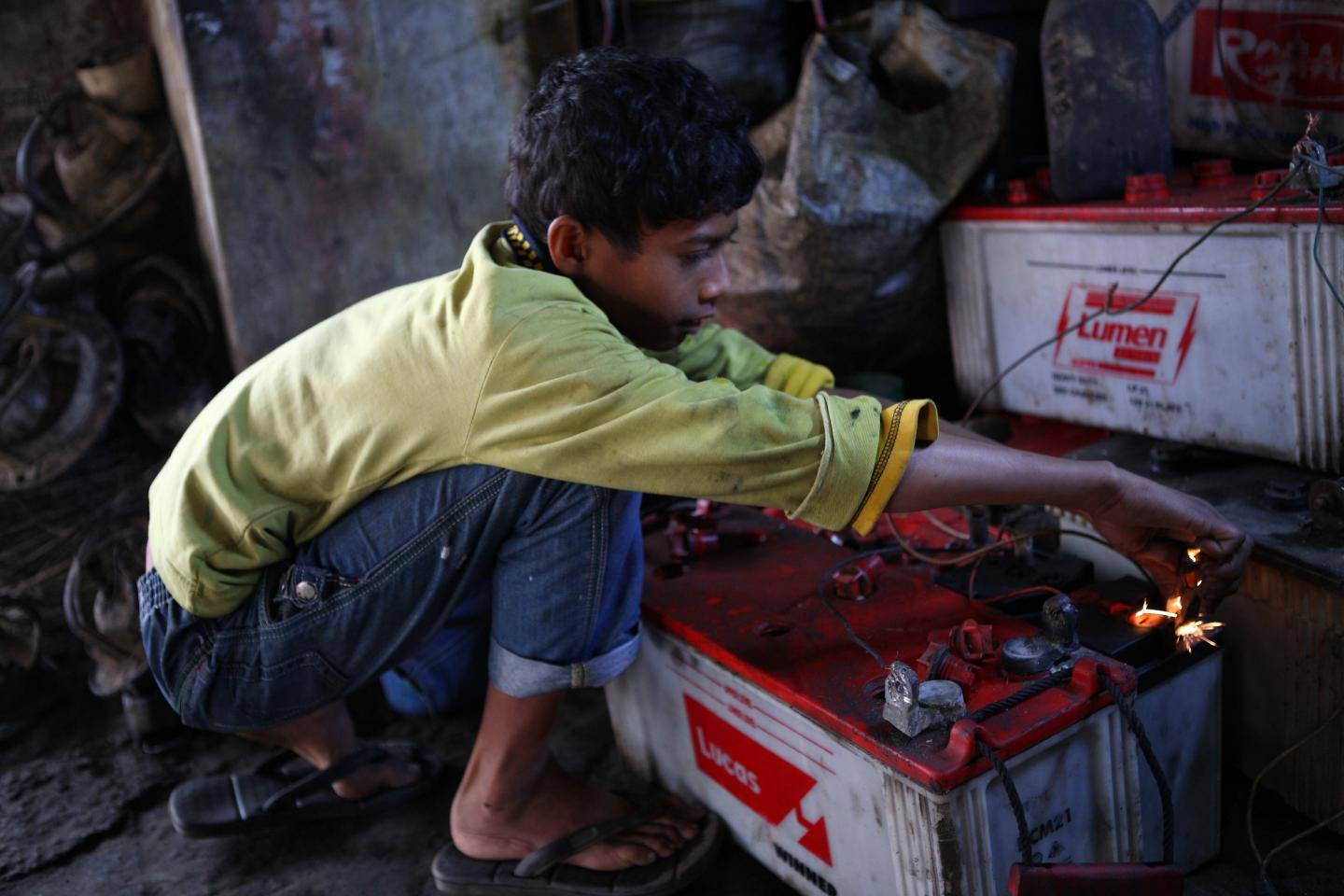 Al Amin, 10, works at a garage where he repairs batteries near the Tangail New Bus Stand on 1 February 2014.