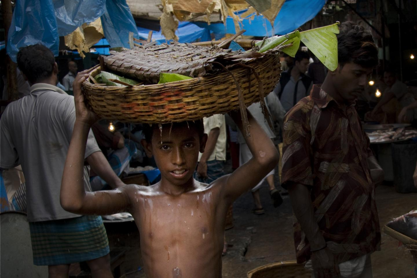 Child labourer Faisal Hosain carries a basket on his head at Dhaka's Mirpur fish market.