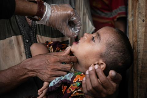 Bangladesh. A red Vitamin-A supplement pill being administered to a 4-year-old Rohingya child