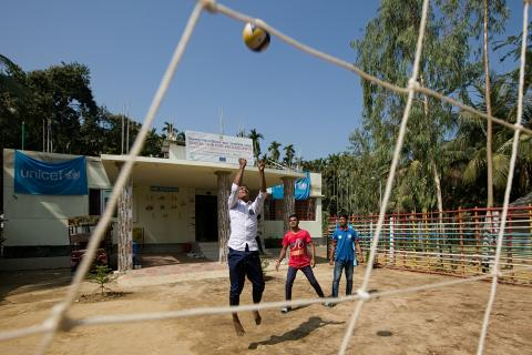 Boys from the host community take advantage of the clear blue sky to hit a volleyball back and forth over a net located in front yard of the hub.