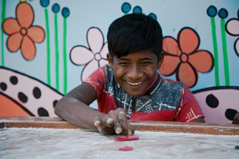 Bangladesh. A teenage boy plays at a social hub for adolescents as agents of peace and stability.