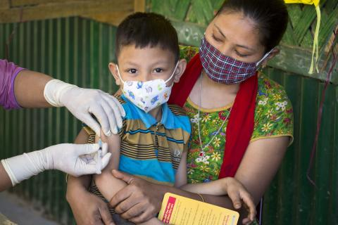 Bisakha Chakma brings her youngest son Tuhin Marma (7) for a measles-rubella vaccination in Rangamati during the national vaccination campaign.
