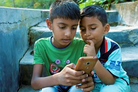 Bangladesh. Children browse the internet through a smartphone.