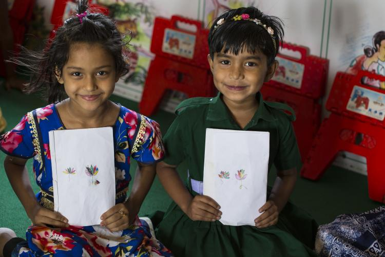 Bangladesh. Two school going girls with their drawings.