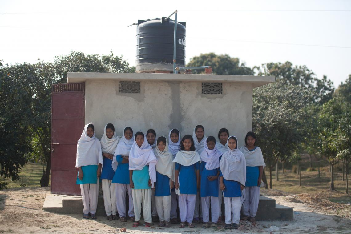 Students stand in front of a latrine facility built with support from UNICEF at Krishnopur High School, Rokonpur, Chapai Nawabganj.