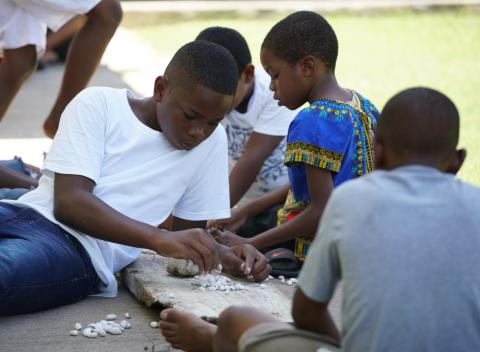 A group of boys prepare sea shells to be used as part of their Jonkunnu costumes.