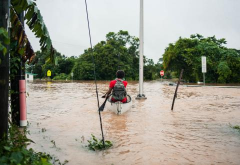 Belize: a young man navigates flood water in a canoe