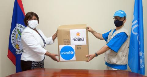 A UNICEF representative hands over a box containing COVID-19 testing kits to a representative from the Ministry of Health in Belize.