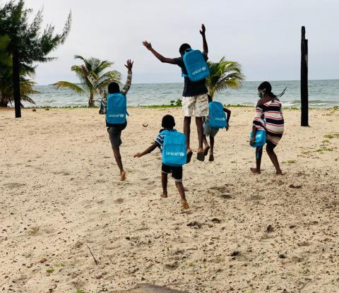 Belize: children wearing blue UNICEF backpacks run and jump on a beach.